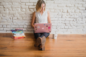 Girl sat on wooden floor leaning against white-painted brick wall. Working on pink laptop with a pile of books on her right and a coffee cup to her left.